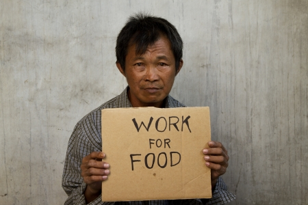 mendicante possesso di un pezzo di cartone ondulato, di fronte a uno sfondo grunge