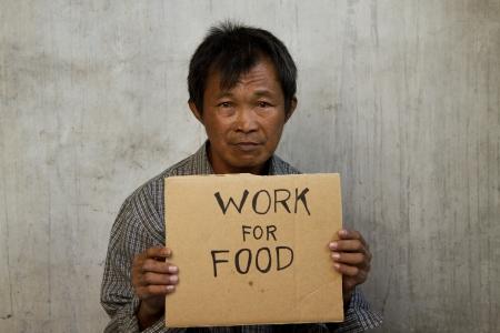 hombre pobre: mendigo con un pedazo de cartón corrugado, delante de un fondo grunge Foto de archivo