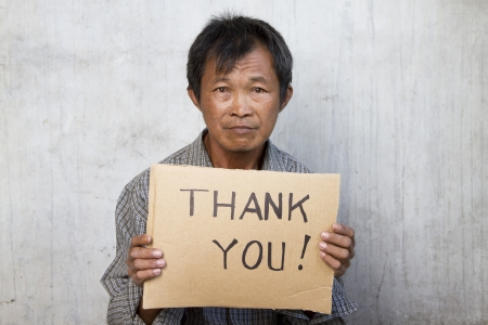 impoverished: thank you message in a carton hold by an old man Stock Photo