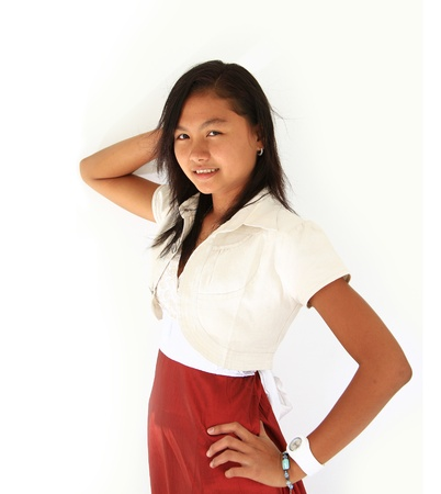 10 12 years: Portrait of Asian teen girl with thumbs in pockets standing against white background