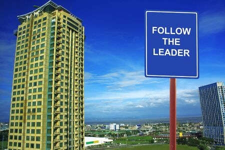 urging: A road sign urging  Follow the Leader   Editorial