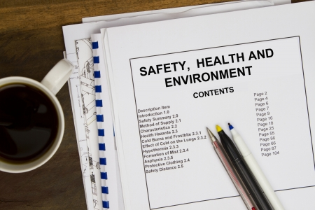 Safety, health and environment with coffee and blueprints.