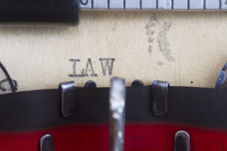 pronounce: Law printed on a vintage paper macro shot. Stock Photo