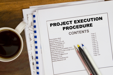 Projct execution pocedure document with coffee and bluepints.