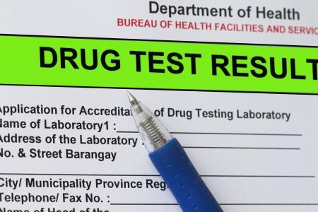 Macro shot of Drug test result form with blue pen