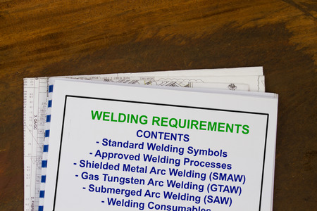 manila envelop: Welding requirements manual with blueprints in a wood texture background.