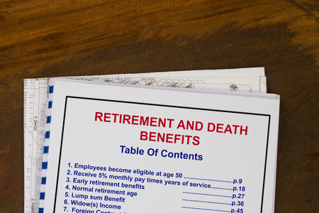 eligible: Retirement and death benefits  training manual with blueprints in a wood texture background.