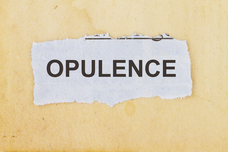 Opulence newspaper cutout in an old paper background. Stock Photo