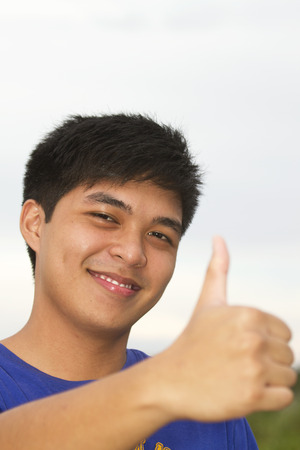 conform: Young teen with gesture thumbs up in an outdoor background.
