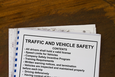 manila envelop: Traffic and vehicle safety basic training manual with blueprints in a wood texture background.