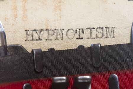 Hypnotism  typed in an old vintage paper macro shot. Stock Photo