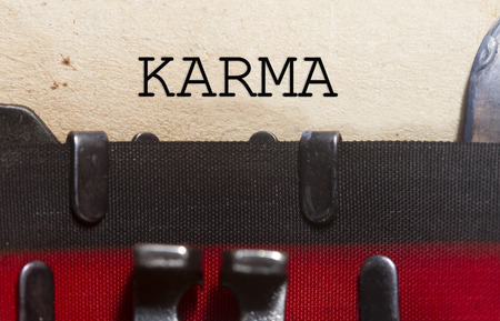 Karma belief   typed on an old vintage paper with od typewriter font.