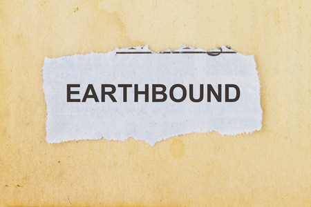 Earthbound newspaper cutout in an old paper background.
