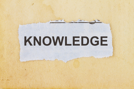 Knowledge newspaper cutout in an old paper background. Stock Photo