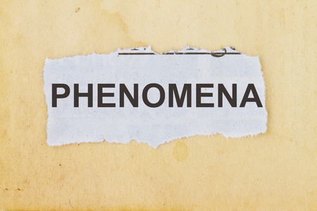 observable: PHENOMENA  newspaper cutout in an old paper background. Stock Photo
