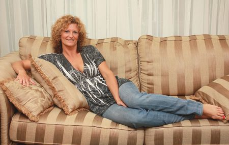 sofa: Beautiful woman laying on a sofa