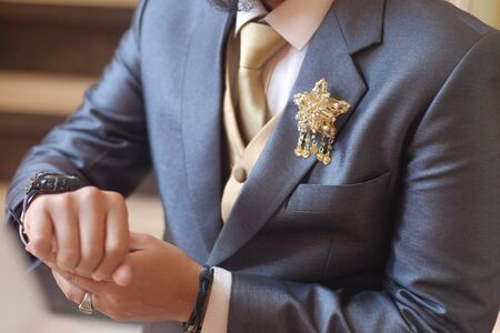 Man in dark grey suit two bottons golden star brooch, checking whatch, close up