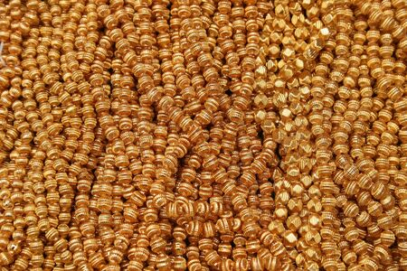 Strings of gold beads for sale at the outdoor craft market in Otavalo, Ecuador