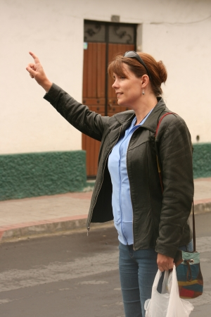 flagging: Attractive woman dressed in casual clothes flagging down a taxi or a bus in Cotacachi, Ecuador Stock Photo