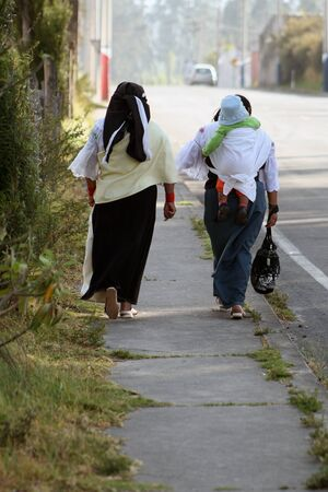 sandels: Three generations of Ecuadorian women walking down the street in Cotacachi, Ecuador