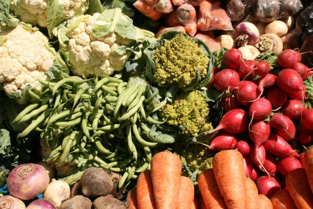 An assortment of vegetables including cauliflower, romanesco, green beans, radishes, parsnips and onions for sale at the outdoor food market in Otavalo, Ecuador Banco de Imagens