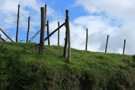 A barbed wire fence stretching over a hill in a farmers pasture in Cotacachi, Ecuador Stock Photo - 17117767