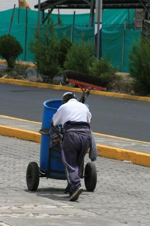 garbage bin: Un limpiador de calle empujando un cubo de la basura por una calle de Cotacachi, Ecuador