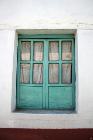 A wooden window with green paint set into a concrete wall in Otavalo, Ecuador Stock fotó