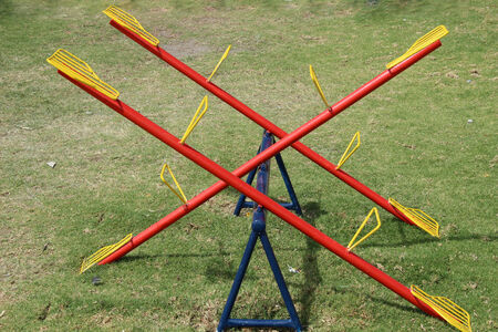 totter: A yellow, red and blue teeter totter in a childrens playground in Cotacachi, Ecuador
