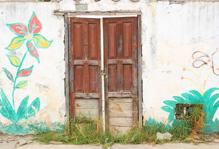 A weathered red door in a wall with a painted flower in Cotacachi Ecuador