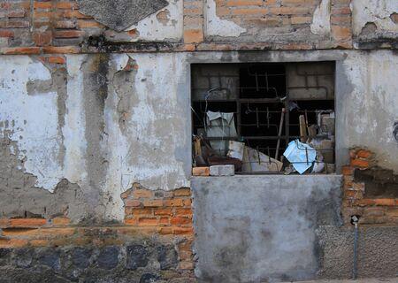A broken window in the wall of a building in Cotacachi Ecuador Фото со стока
