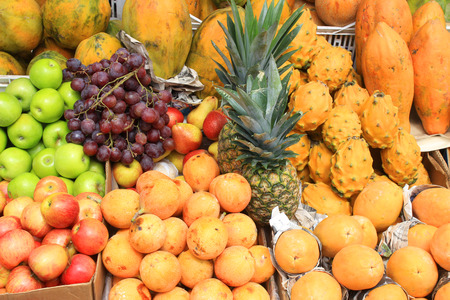Exotic fruit including granadilla, pitahaya, babaco, pineapple, grapes and apples for sale at the outdoor food market in Otavalo, Ecuador
