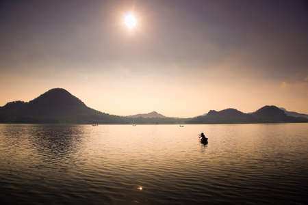 A man fishing with kayak in foggy morning