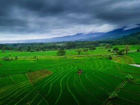 Indonesias natural beauty of Sumatra, where green rice fields with high mountains and beautiful blue clouds for a relaxing trip aerial photo
