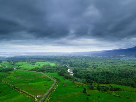 Indonesias natural beauty of Sumatra, where green rice fields with high mountains and beautiful blue clouds for a relaxing trip aerial photo in morning