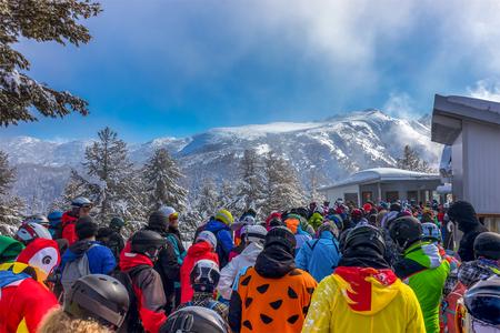 Viele Skifahrer warten auf Skilift mit schöner Aussicht auf den schneebedeckten Berg Pirin in Bansko - Bulgarien.