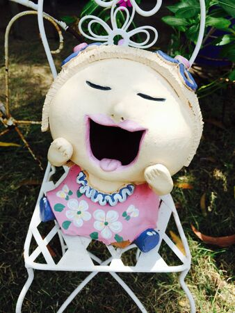 doll: Smiling doll in garden Stock Photo