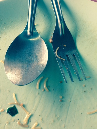 discus: A spoon and fork are placed on a plate that has been finished eating