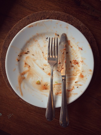 A spoon and fork are placed on a plate that has been finished eating
