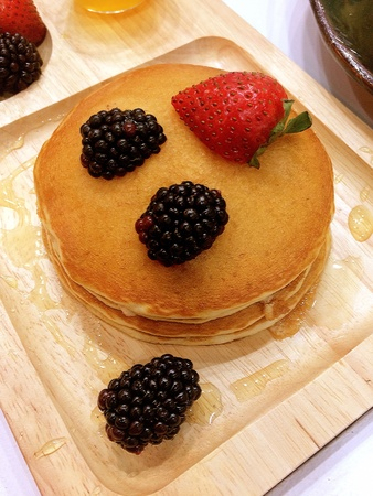 Pancakes decorated with strawberries and berries are placed on a beautiful wooden tray to eat Stock Photo