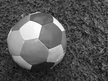 black: black and white photo of football on the field