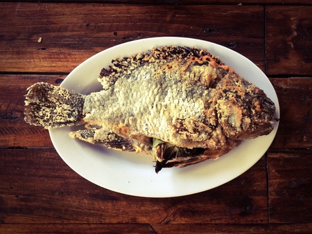 Grilled Fish is a famous seafood dish put on a wooden table with copy space
