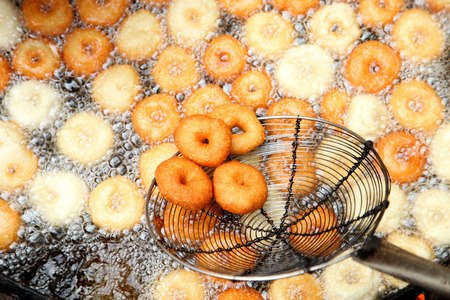 Deep frying medu vada in the pan. Medu Vada is a savoury snack from South India, very common street food in the India. Stock Photo