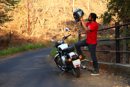 Young man standing near motorbike . 版權商用圖片