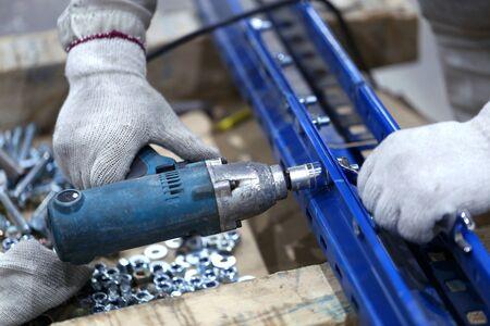 One warehouse worker in with power tool tightening screw during rack arrangement erection work