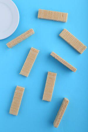 Tasty wafer sticks on Blue background, flat lay. Sweet food