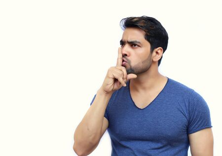noiseless: Young Indian suited man with a gesture of shh - isolated white background