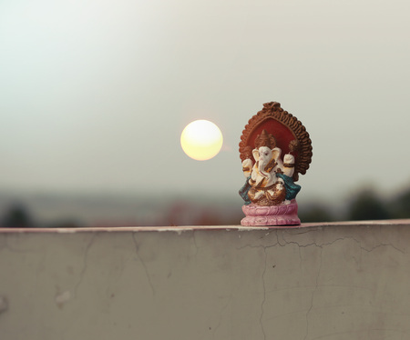 Beautiful idols of Lord Ganesha isolated on a sunset background