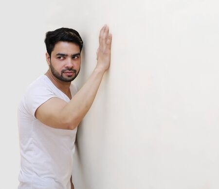 male body: Portrait of thoughtful young handsome Indian man against the white Wall Stock Photo