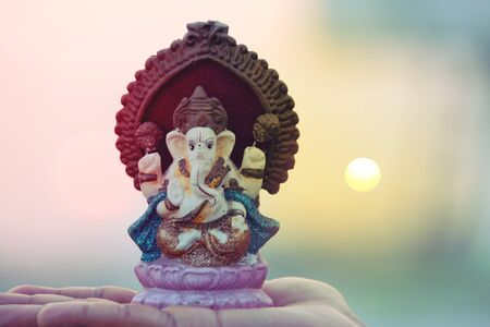 Beautiful idols of Lord Ganesha isolated on a sunset background.